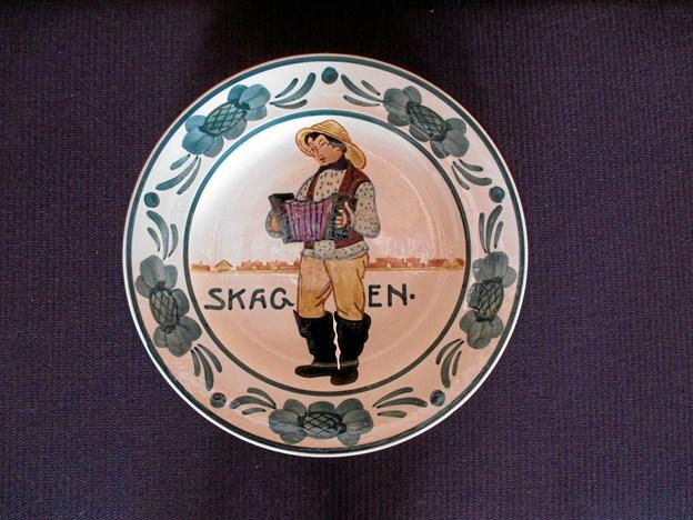 Spisesalen på Klitgaarden er smykket med købstadsplatter udført af maleren Harald Slott-Møller, men derudover findes der også en serie folkedragtsplatter, som den enarmede maler Christian Joachim (1870-1943) er mester for. Alle platter blev lavet på fabrikken Aluminia 1903-1913. LOKALHISTORISK ARKIV SKAGEN
