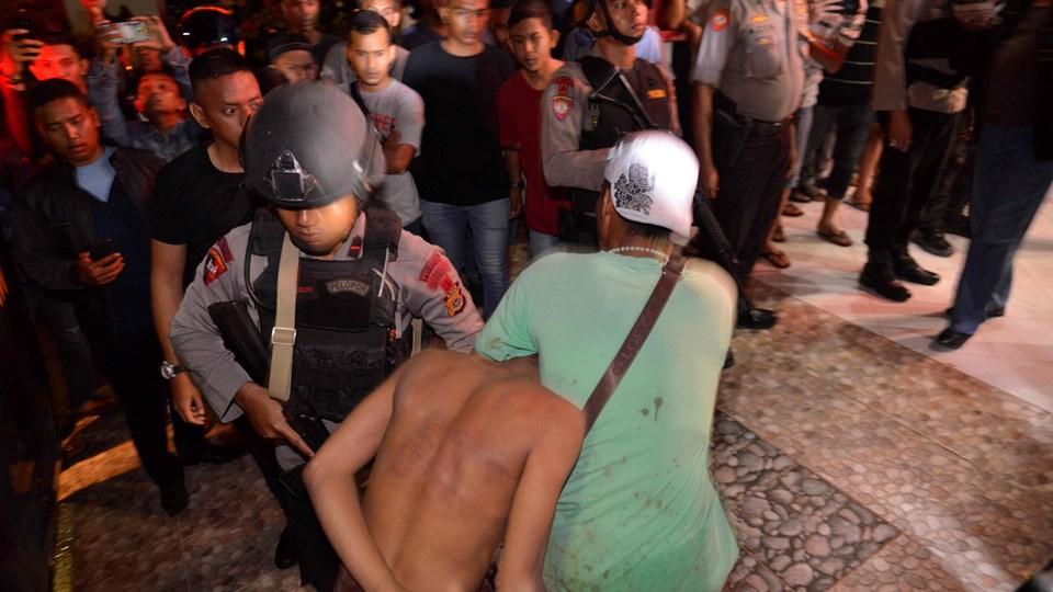 Politibetjente anholder her en af de i alt 113 indsatte, der torsdag aften flygtede fra et fængsel i Indonesien.