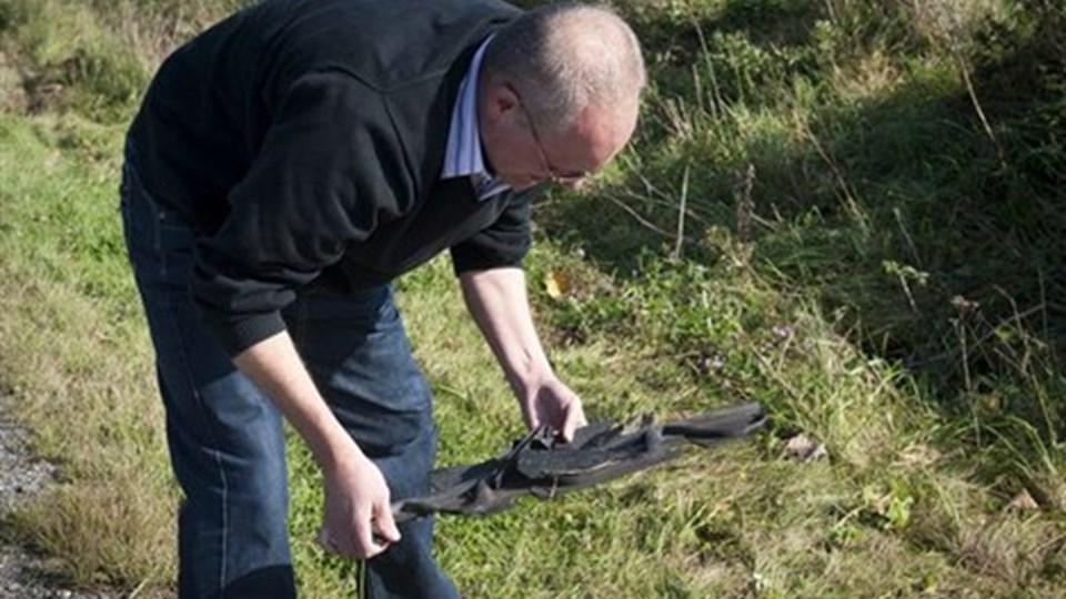 Kris' far - Per Simonsen - er tilbage på ulykkesstedet. Her finder han et stykke metal fra sin søns scooter. Foto: Carl Th. Poulsen