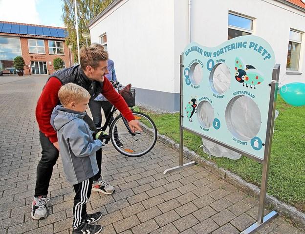 Man kunne også dyste i affaldskast. Her er det 7-årige Kristian, der forsøger sig godt hjulpet af Morten Ulltveit-Moe fra AVV. Kristian klarede sig så godt, at han vandt et gavekort på 50 kroner. Foto: Jørgen Ingvardsen
