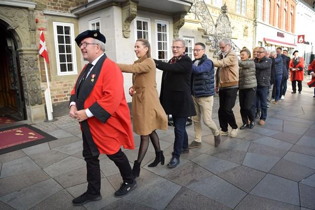 Socialdemokratiets formand Mette Frederiksen har lagt hånden på skulderen af Peter Reinau, der har til opgave at føre de nye medlemmer af lavet på den obligatoriske gåtur rundt om stenhuset.