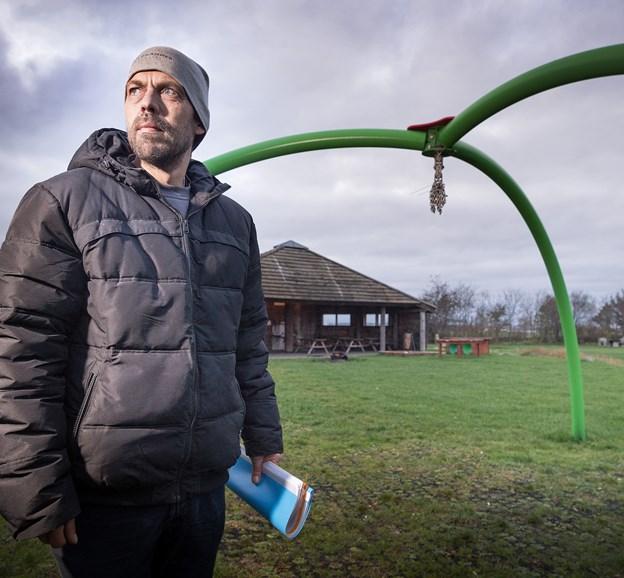 Peter Andersen Lundtoft foran det tomme gyngestativ. Han er træt af, at nogen ikke kan lade gyngen og resten af tingene i Jægerum Søpark være. Foto: Torben Hansen