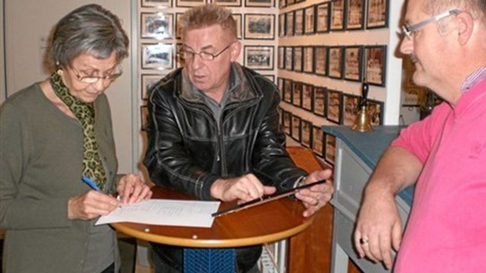 Frank Bæhrenz (i midten) oplyser navne til Martha Pedersen fra et konfirmationsbillede. Til højre formand i Biersted/Nørhalne Lokalhistoriske Forening, Jørgen Pedersen. Foto: Anne-Mitha Sørensen.