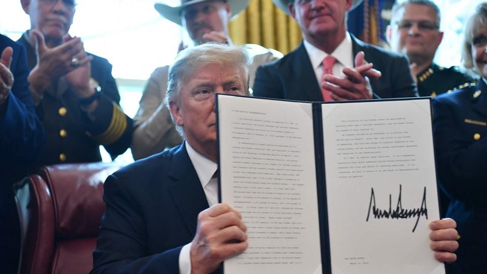 Præsident Donald Trump viser dokumentet frem, der viser, at han har nedlagt veto mod Kongressen afgørelse. Han er omgivet af folk fra ordensmagten, der skal håndhæve hans beslutning om nødret ved grænsen til Mexico.