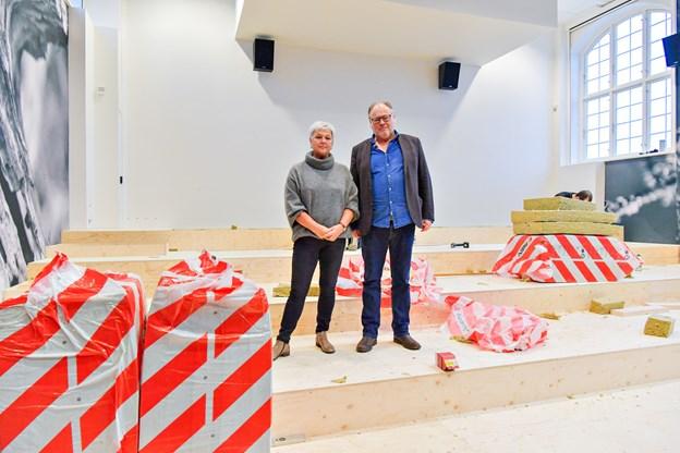 Formand for Skagen Bio, Kirsten Leth og kulturhuschef Lars Ilum glæder sig til det færdige resultat. I ugen der gik, knoklede håndværkerne for at få de nye stole monteret på podiet i salen. Den officielle indvielse sker mandag 10. december. Foto: Kim Dahl Hansen