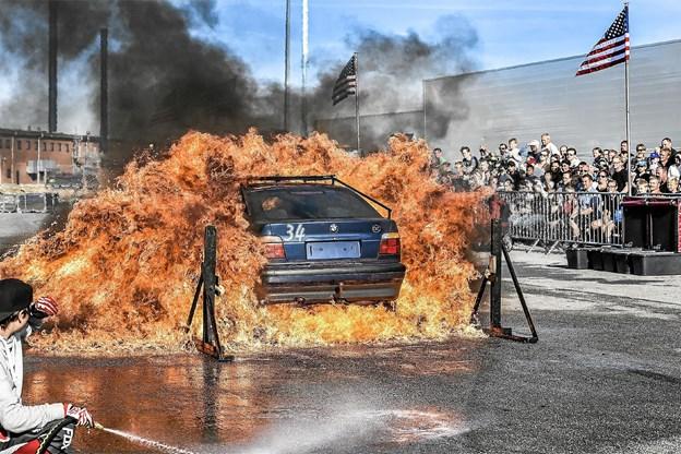 Voldsomt så det ud, når bilerne drønede gennem flammer med folk på taget og bagefter bilerne. Men hjælperne stod klar med vand til at slukke bensin bålene. Foto: Ole Iversen