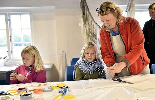 Grethe Wittrock hjælper børnene med at skabe flotte fuglefjer ud af sejldug i en kunstnerisk proces. Sofia Seneca, Vejle og Emilie K. Olsen, Aarhus er i fuld gang. Foto: Ole Iversen