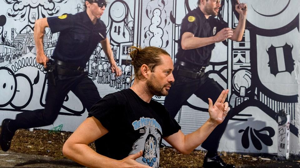 Fordoblingens kunst. Chaz Barrissonn - den ene del af street art duoen London Police - her iscensat foran Søren Solkærs portræt af duoen. Som i sine øvrige portrætter har Solkær arrangeret kunstnerne, så de indgår i sammenspil med deres egne værker. Til dette portræt lejede han politiuniformer i USA, der selvfølgelig kom med ægte pistoler. Foto: Nicholas Cho Meier