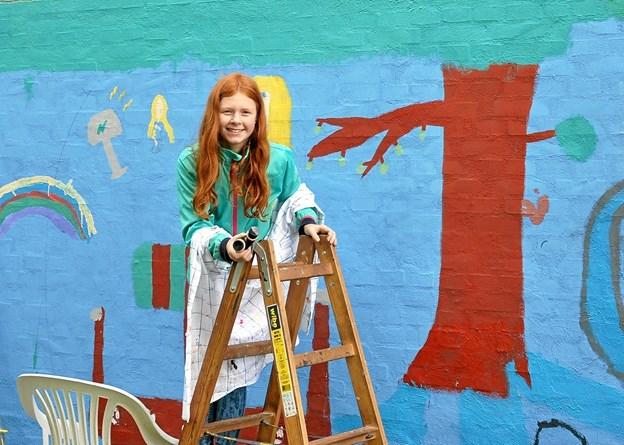 Nicoline er på vej op ad stigen for at male videre på Verdenstræet Yggdrasil, hvis krone strækker sig på langs af muren. Foto: Ole Torp
