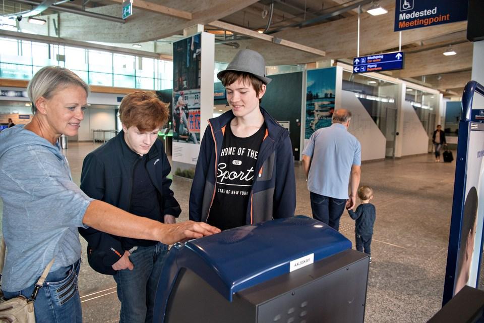 Lærer Anette Holt studerer check-in-automaten sammen med Frederik WInther (tv) og Emil Pedersen.