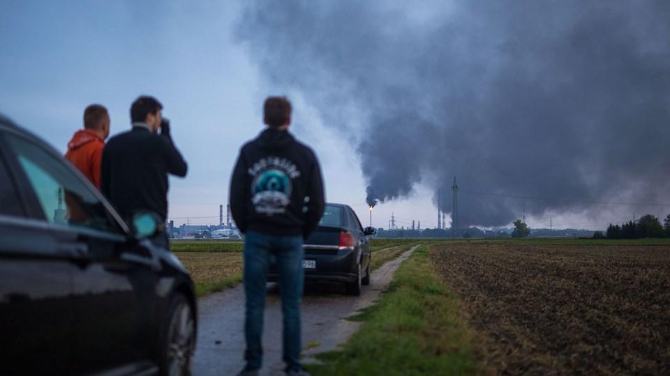 Bilister er stoppet op for at se røgsøjlerne fra et brændende raffinaderi i Bayern nær storbyen Ingolstadt. Otte mennesker blev kvæstet ved en eksplosion i raffinaderiet tidligt lørdag morgen. Foto: Lino Mirgeler/Ritzau Scanpix