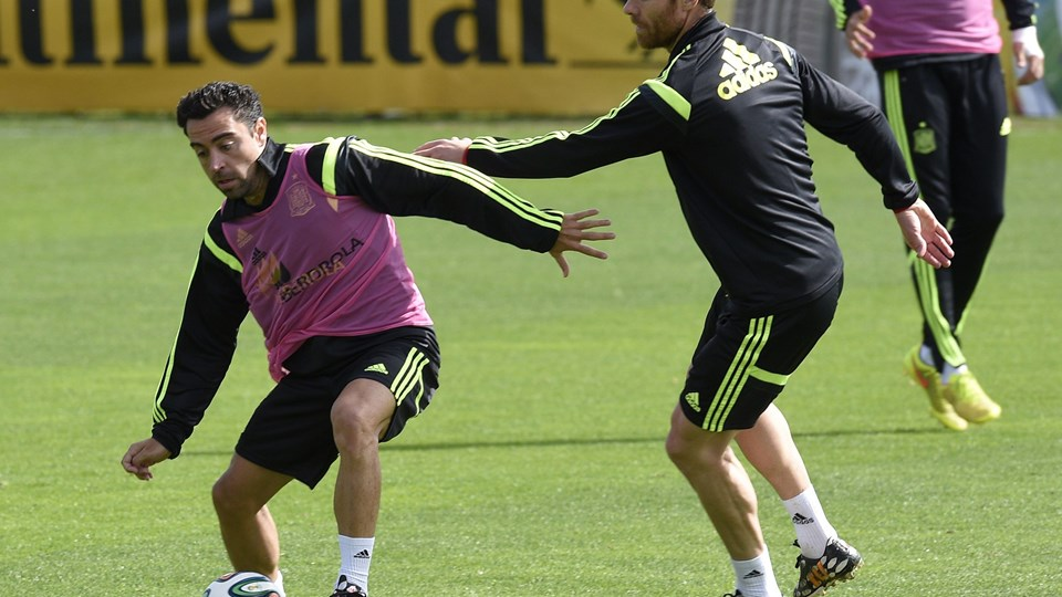 Spain's midfielder Xavi Hernandez (L) vies with Spain's midfielder Xabi Alonso (R) during a training session on June 21, 2014, at the CT do Caju in Curitiba during the 2014 FIFA World Cup.  AFP PHOTO/ LLUIS GENE