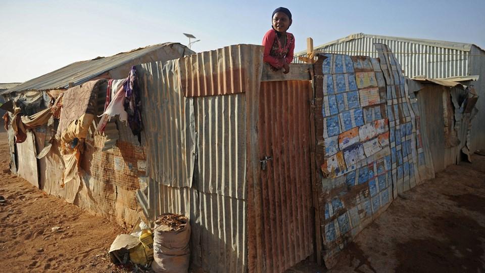 Danmark giver 100 millioner kroner til Dansk Flygtningehjælp, som støtter hjemvendte somaliere i Somalia. Her kigger en somalisk pige ud fra sin skrøbelige bolig i en lejr for internt fordrevne i Garowe, som ligger i den nordlige stat Puntland, som er brudt ud af Somalia. Foto: Scanpix/Mohamed Abdiwahab/afp Photo