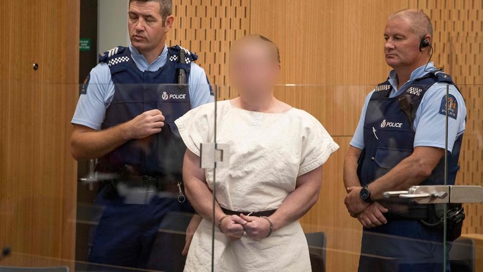 Under et kortvarigt retsmøde lørdag blev Brenton Tarrant (i hvid fængselsdragt) sigtet for drab i forbindelse med massakrerne fredag i Christchurch.