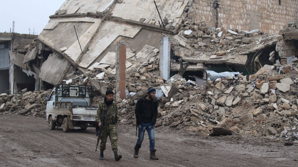 Rebel fighters walk near damaged buildings in al-Rai town, northern Aleppo countryside Foto: Reuters/Khalil Ashawi