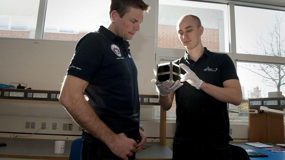 I marts besøgte Andreas Mogensen (til venstre) AAU og fik demonstreret AAUSAT5. På mandag kommer han igen, når satellitten sammen med en anden Aalborg-satellit skal sendes i kredsløb fra ISS. Arkivfoto: Anne Mette Welling