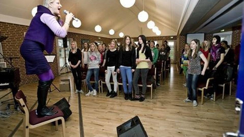 Tina Buchholtz styrede med hård hånd 150 unge fra Støvring til gospelworkshop tirsdag i sognegården. Her skal de skrue op!Foto: Grete Dahl