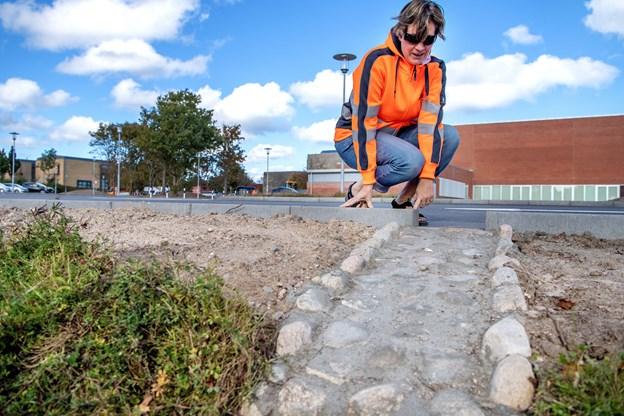 Jane R. Olesen fra Park & Vej viser, hvor regnvandet ledes væk fra pladsen og ud i grøften.