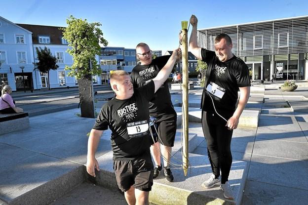 """Team Simfit i gang på Havnetorvet med """"hundeproppen"""" balancerende med vand på en hegnspæl. Foto: Ole Iversen"""