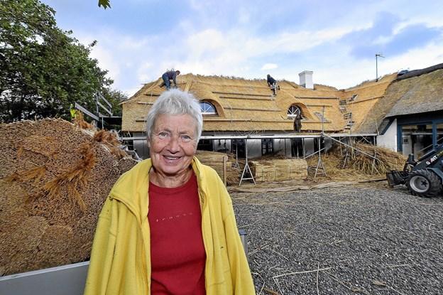 Birgit Liltoft glæder sig over husets nye stråtag. Til højre på sidelængen ses et ældre stråtag lagt år tilbage. Foto: Ole Iversen