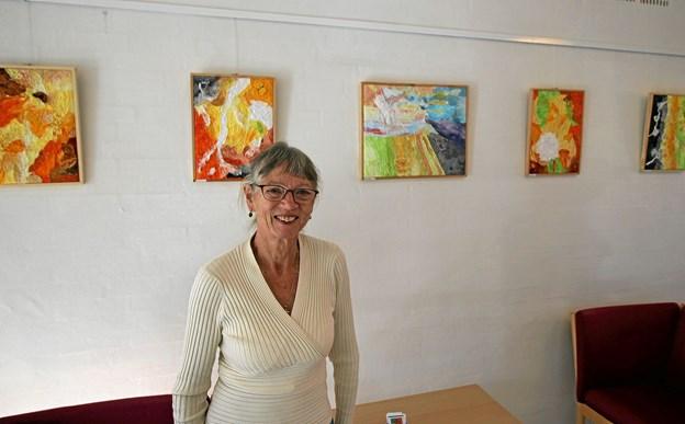Eva Nielsen foran nogle af sine billeder, der i denne tid udstilles i Dronninglund Sognegård. Foto: Jørgen Ingvardsen