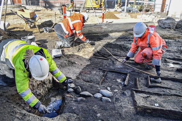 Kister og knoglerester ligger i lag på Budolfi Plads: Se hvad der dukkede op i solskinnet
