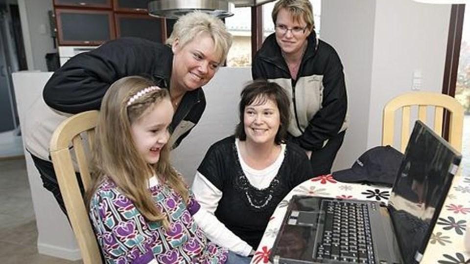 Birgitte Christensen (th.) og Tina Svanhede fra Ønskefonden kom med gaven til Simone Nielsen. Tina Nielsen ser til, mens datteren pakker ud. Foto: Erik Sahl