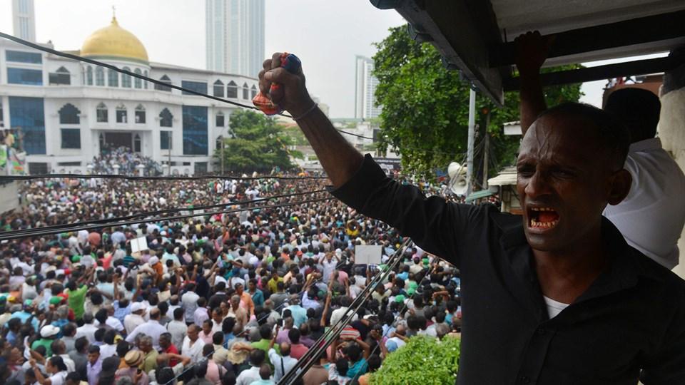 En tilhænger af Sri Lankas afsatte premierminister Ranil Wickremesinghe ses her under en demonstration søndag mod præsidentens beslutning. Titusindvis deltog i protesterne og blokerede store dele af trafikken i hovedstaden Colombo. (Arkiv).