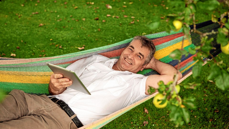 Happy man reading a digital tablet in a garden with green grass