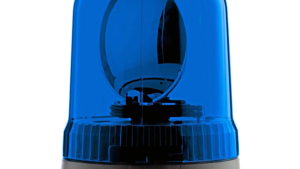Blue rotating beacon on white reflective background.