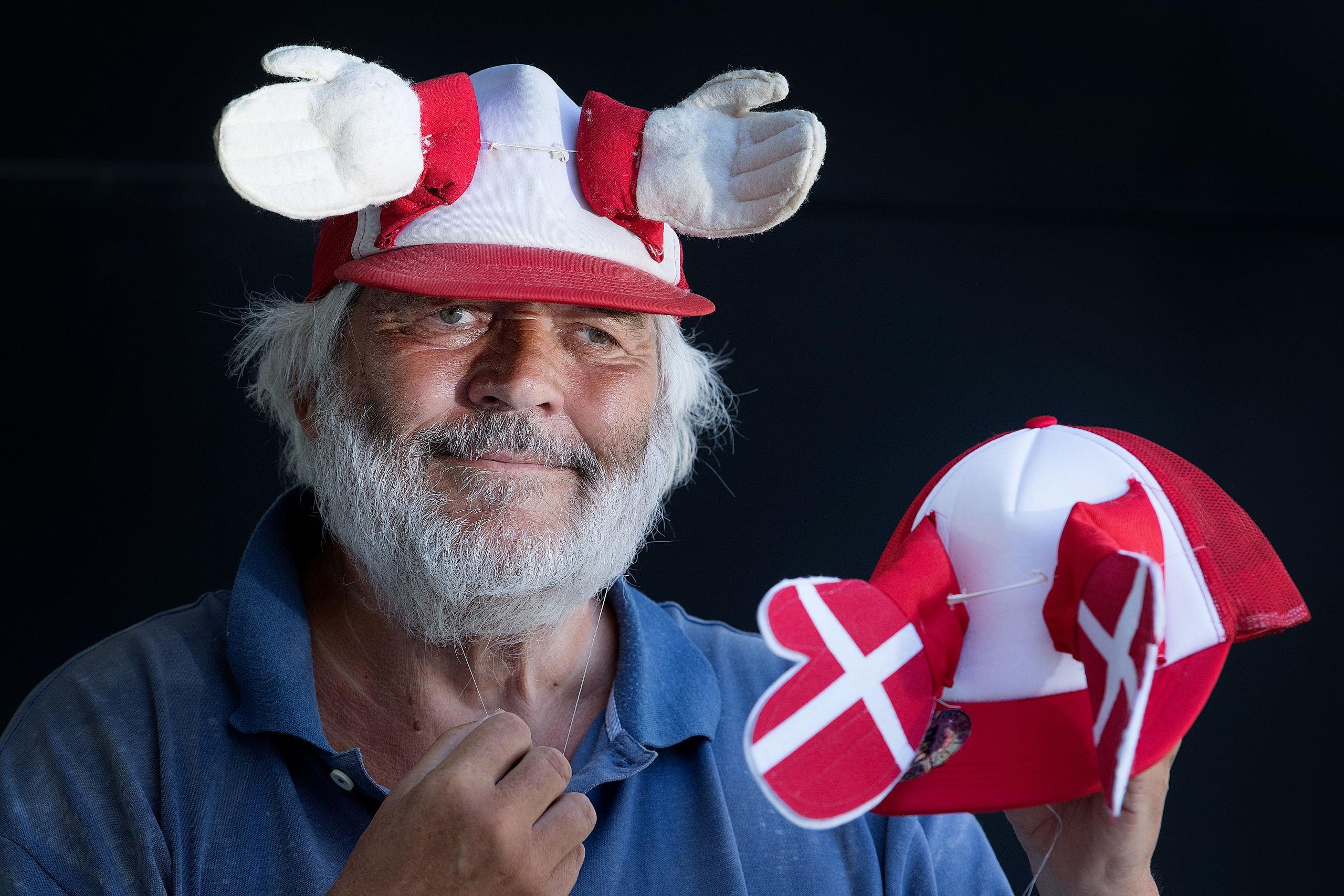 Peter Wendelboe med den første klaphat fra 1981 på hovedet. I hånden den ny, som er forsynet med et DBU-logo. Foto: Torben Hansen