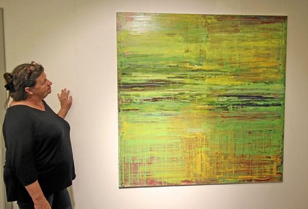 Maleren Ingun Hansen ved et af sine farvestrålende værker, man kan opleve på den aktuelle udstilling. Foto: Jørgen Ingvardsen