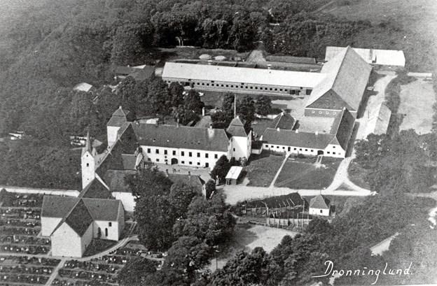 Luftfoto af Dronninglund Slot og Hovedgården omkring 1945. Ved indgangsporten kan man se vagtbarakken og skilderhuset. I forgrunden udenfor slottet store stakke af tørv.