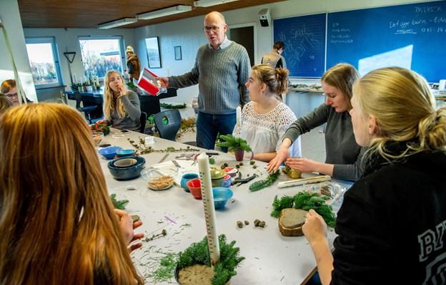 Forstander Karsten Madsen ?deler pebernødder og ?brunkager ud, mens ?Henriette Hansen sidder i ?den hvide trøje og laver ?et kalenderlys.