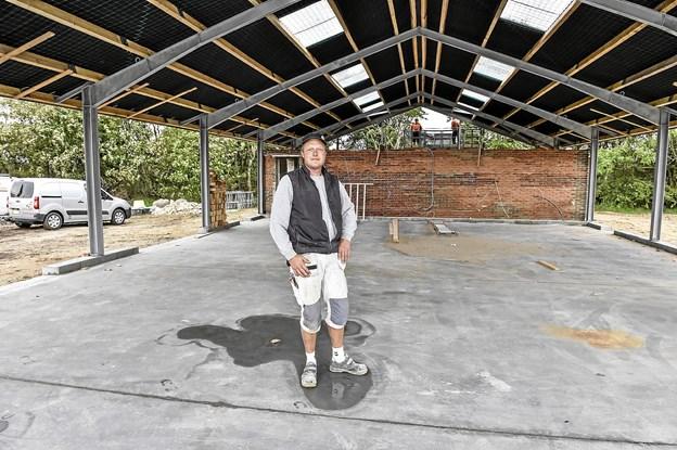 Martin Christensen i den nye hal, der skal huse alt hans grej og materialer. I baggrunden bag muren er velfærdsfaciliteter. Foto: Ole Iversen