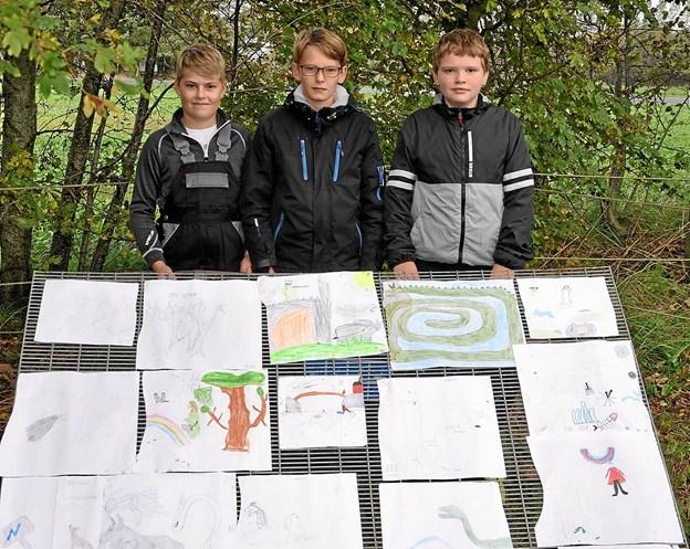 Fra venstre er det Tobias, Tobias og Philip bag udstillingen af de tegninger, som de brugte som forlæg for figurer m.m. på væggen. Foto: Ole Torp