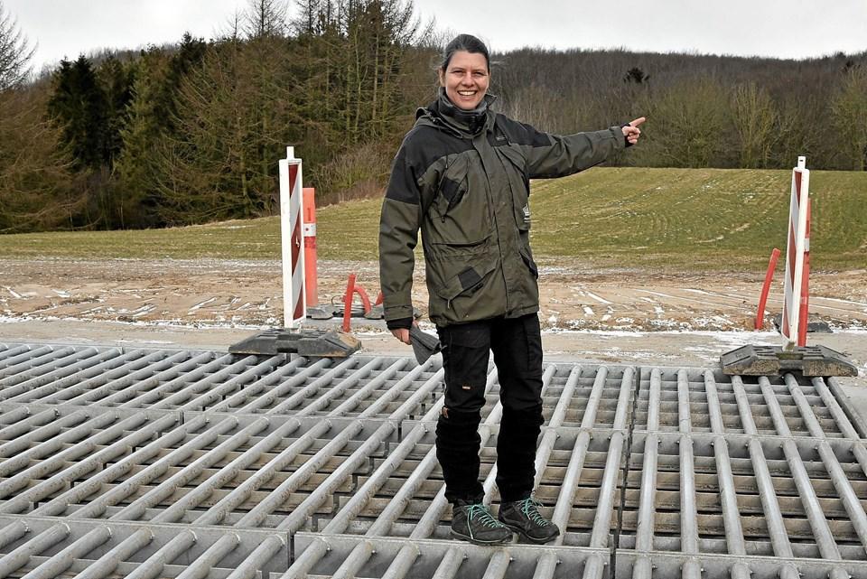 Skovfoged Helene Overby står på en af tre færiste ved dyrehavens nye område i Slotved Skov. Færisten er bygget i meget kraftige materialer med stor afstand mellem stålstolperne. Derfor er der fastsat en højeste hastighed på 20 km/t ved passage. Foto: Niels Helver