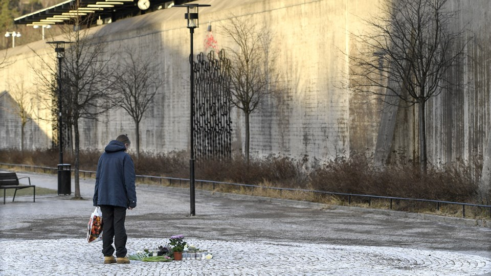 Mennesker har lagt blomster og tændt lys på torvet i Vårby Gård i Stockholm, hvor en 60-årig mand søndag mistede livet, da han samlede en håndgranat op. Foto: Scanpix/10040 Anders Wiklund/tt