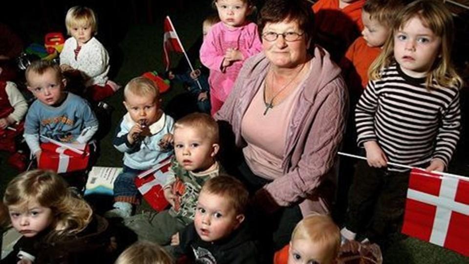 Dagens hovedperson Aase Larsen omgivet af dagplejebørn ved afskedsreceptionen for hende i FDF-huset Skrænten med kollegaeren som arrangører.  FOTO:LARSPAULI