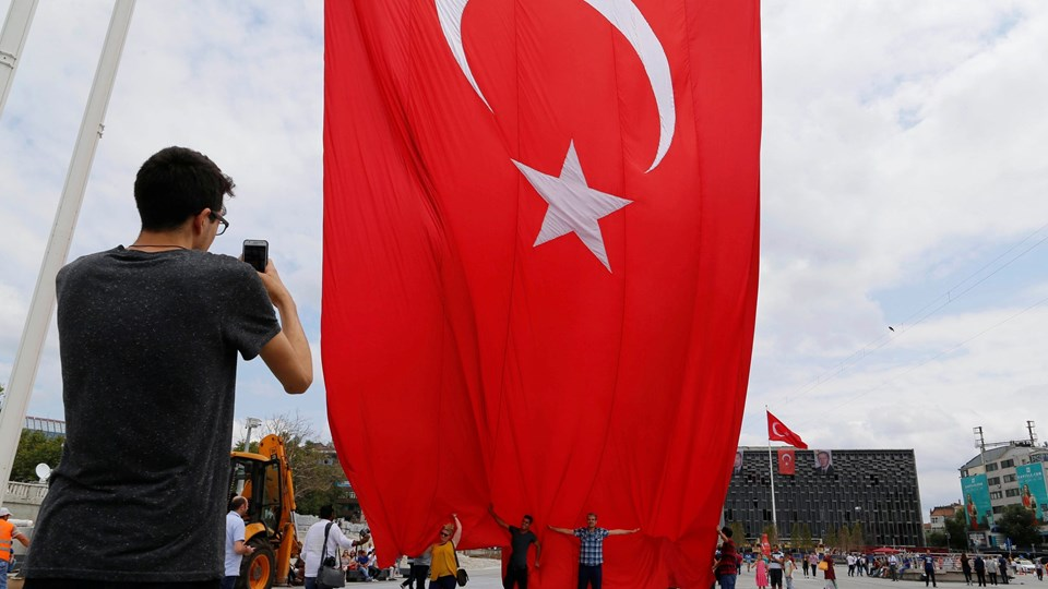 A supporter of Turkish President Tayyip Erdogan takes a picture with the giant Turkish national flag on Taksim Square in Istanbul, Turkey Foto: Reuters/Ammar Awad