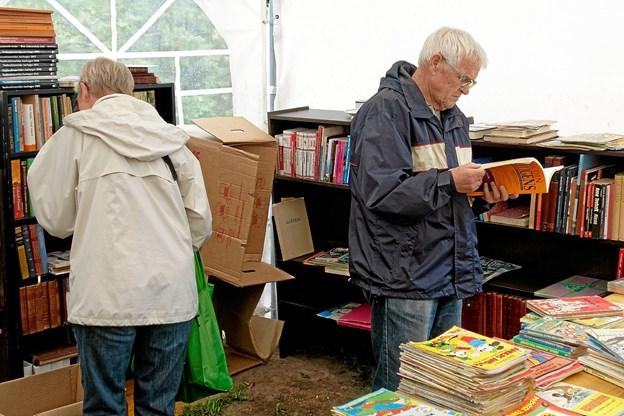 Bogladen var meget velassorteret, og i regnen var der flere, der benyttede lejligheden til en lille læsepause. Foto: Niels Helver