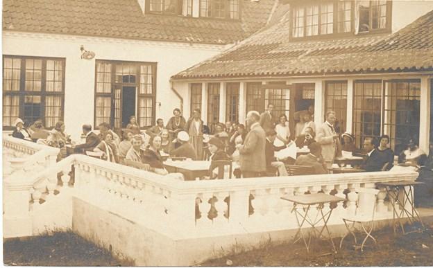 Badegæster af den finere kategori nyder sommeren på verandaen ved Ruths Hotel – tegnet af Julius Berg.